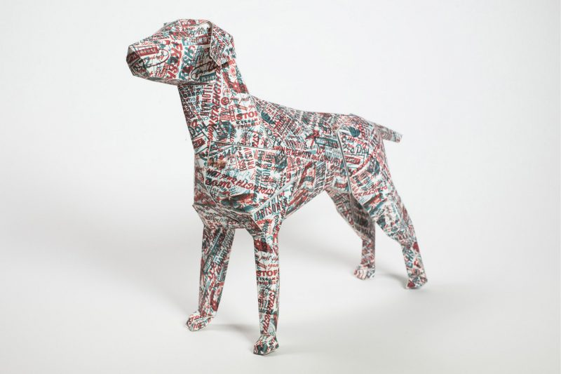 A 3D paper dog model covered in a pattern created using random words in red and blue