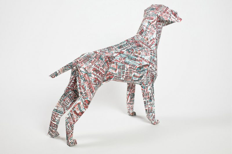 A paper dog model in 3D with a pattern using red and blue random words all over its body.