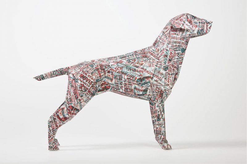 A side view of a 3D paper model of a dog with a pattern using red and blue random words