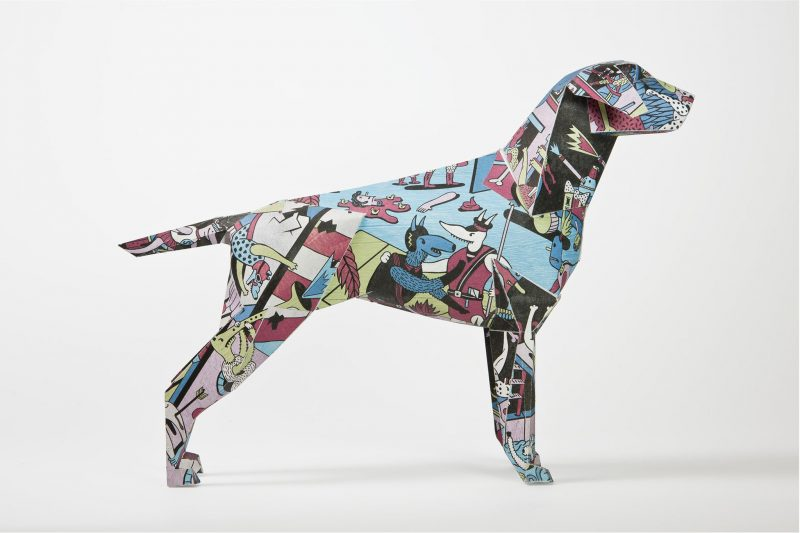 A side view of a 3D model of a paper dog. it has a comic style colourful pattern all over it.