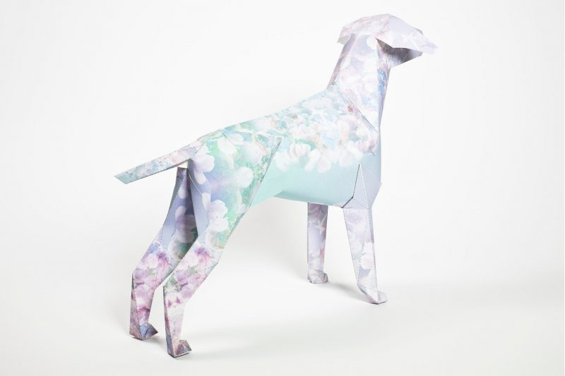A 3D paper dog model that has a light pastel flowers on it with purple and blues