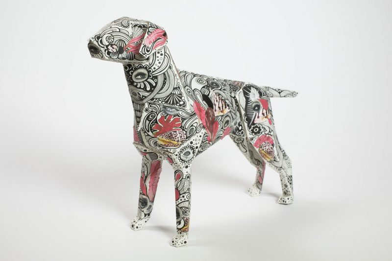 A 3D paper dog model with a black paisley style patter n with pink patches
