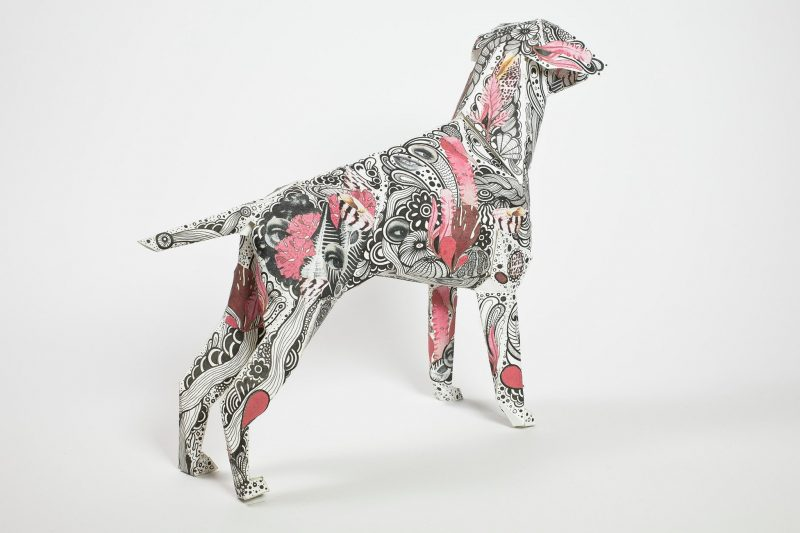A paper dog model with a paisley black pattern and various pink patches around the body.