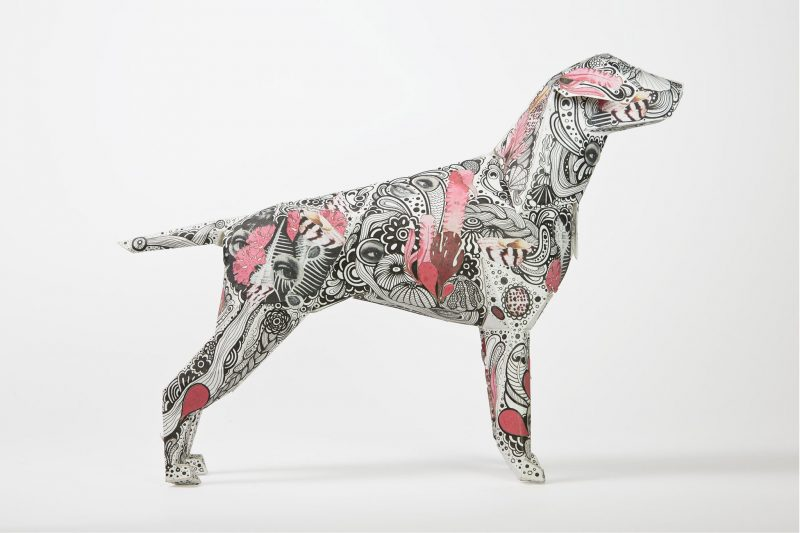 A side view of a 3D paper dog model with a paisley pattern and pink patches.