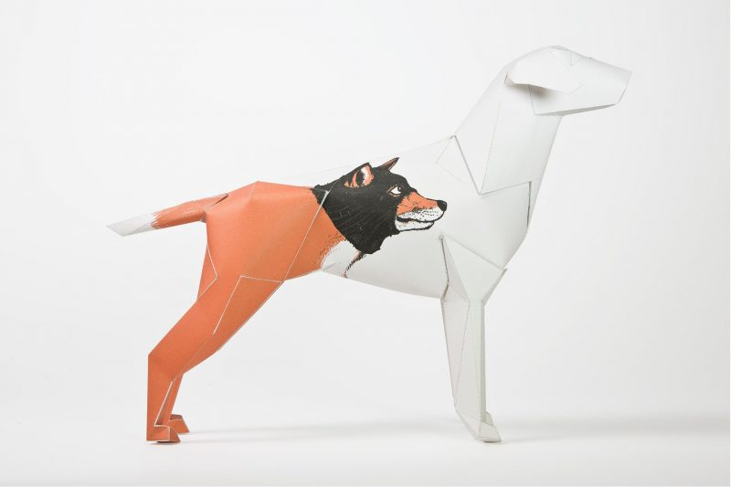 A 3D paper model of a dog that has a wolf face drawn on it.