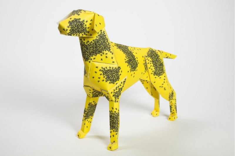 A 3D paper dog model that is yellow with swarms of black bees all over it in different groups.