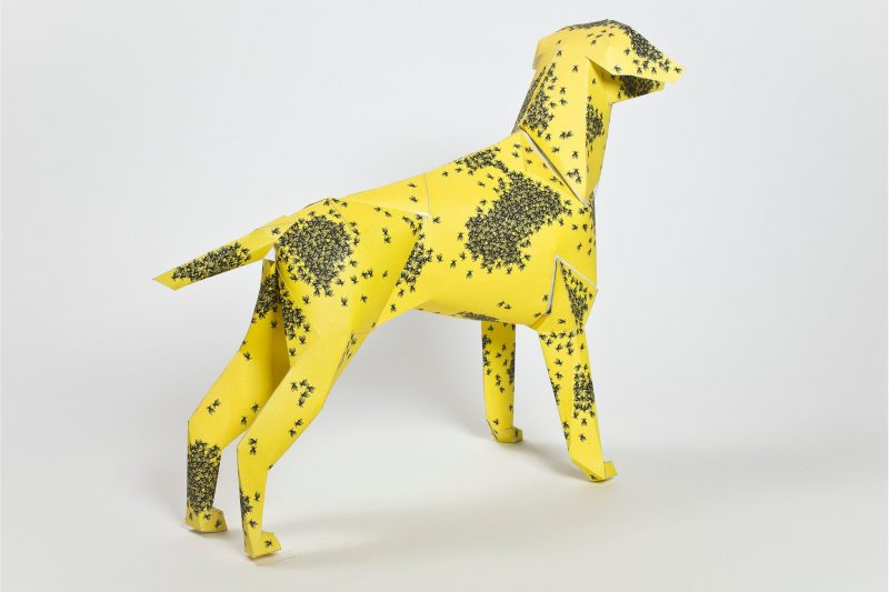 Yellow 3D paper dog model with swarms of black bees over it.