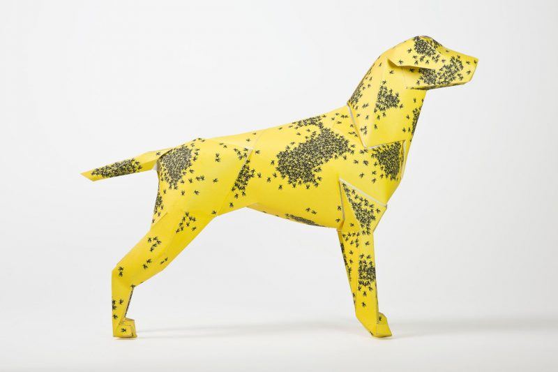 Side view of a yellow paper dog with swarms of bees all over it