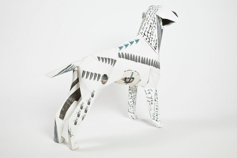 A 3D paper dog model that has a black pattern on it that is inspired by a star constellation