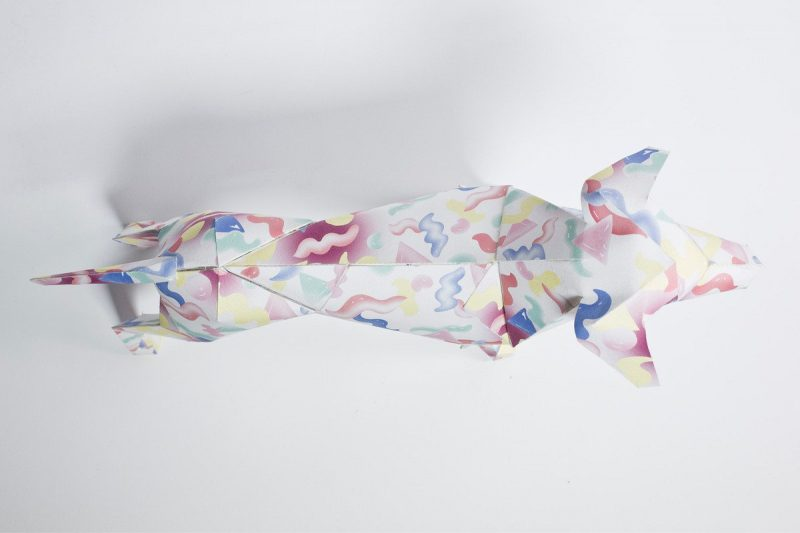 Over head view of a paper dog with red, yellow and blue squiggles