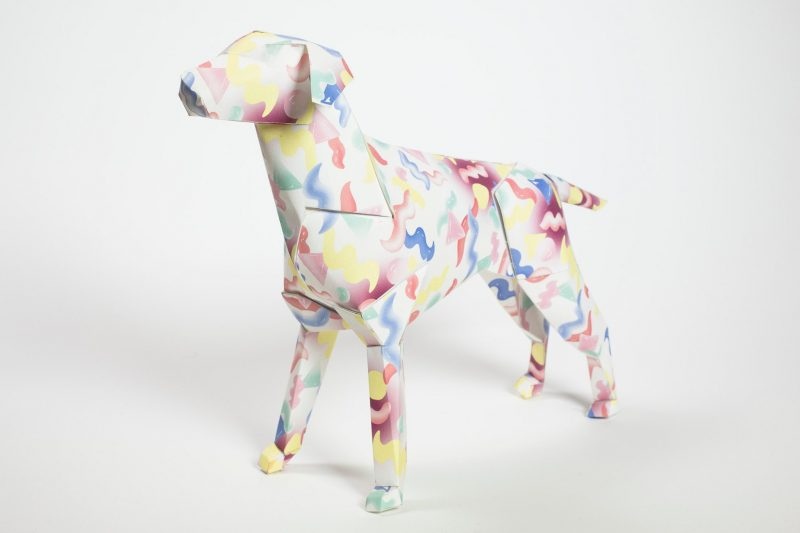 A 3D paper dog model with a pattern of red, blue and yellow squiggles