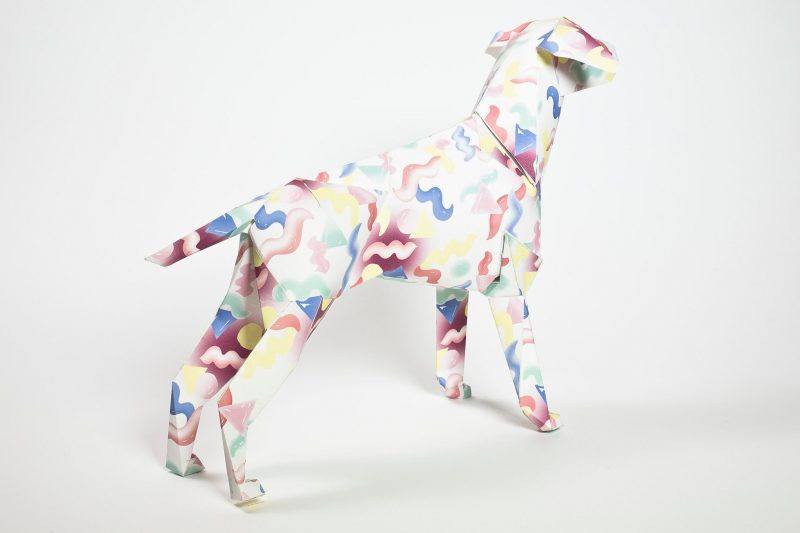 A paper dog model with yellow, blue and red squiggles