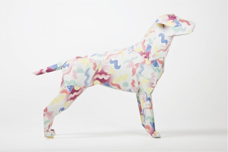 Side view of a paper dog with red, blue and yellow squiggles all over it