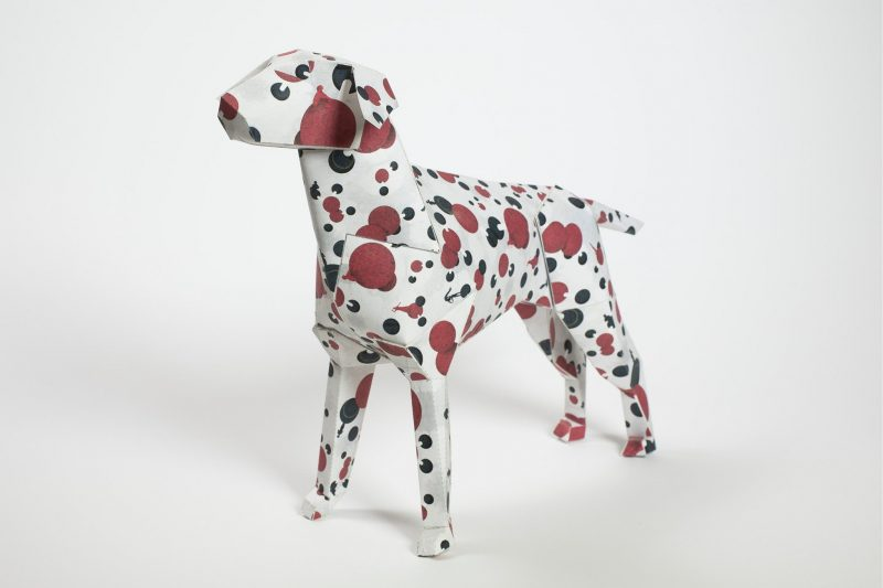Paper 3D model of a dog with red and black spots all over it.