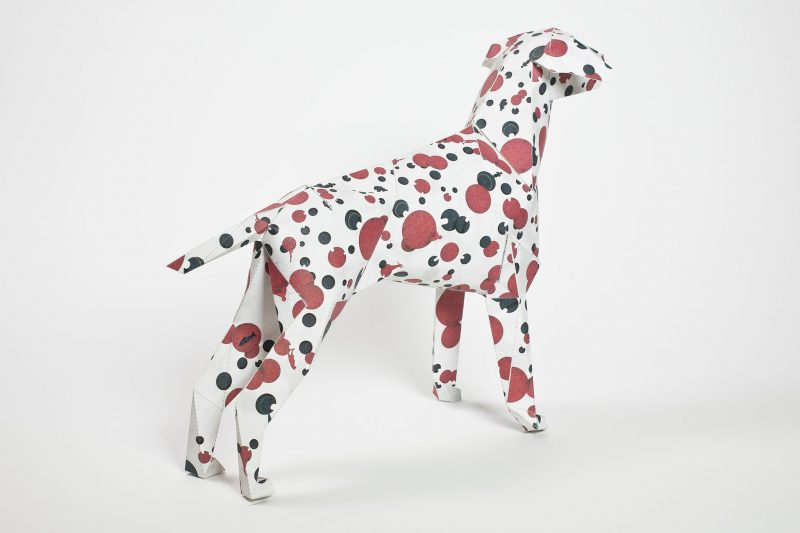 A paper dog model in a 3D format with the dog head facing towards the back right corner. The design on the dog is red and black spots.