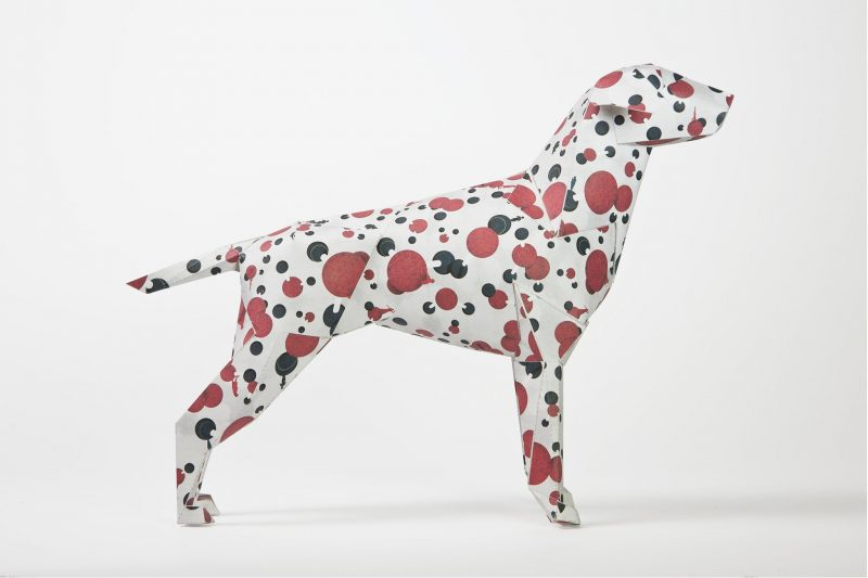 Side view of a paper dog 3D model with red and black spots on it.