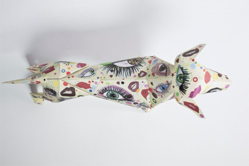Over view of a 3D paper dog that has a colourful pattern consisting of eyes and lips all over it