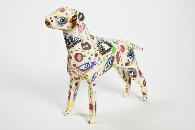 A 3D paper dog model with a multi- coloured pattern with eyes and lips all over it