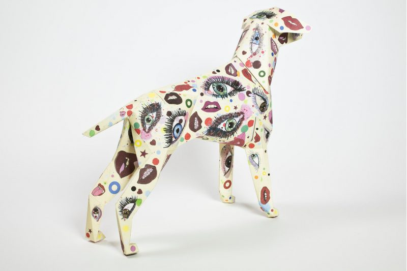 A 3D paper dog model with a pattern that consists of eyes and lips, it is very multi- coloured.