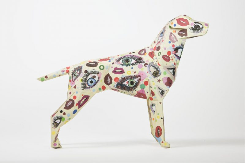 A 3D paper dog model with colourful eyes and lips all over it.
