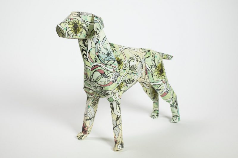A paper dog model with a green vine, leaves and flower design.