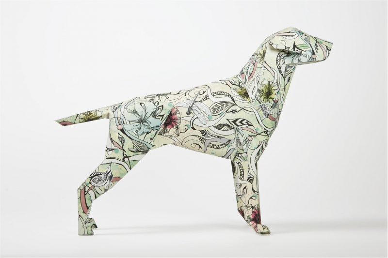 Side view of a 3D paper dog model with leaves, vines and green flowers on it.