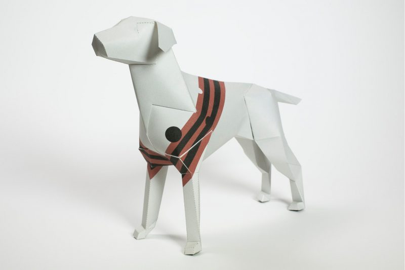 A 3D paper dog model with a 3 red and 2 black stripes around its torso in a alternating colour way.