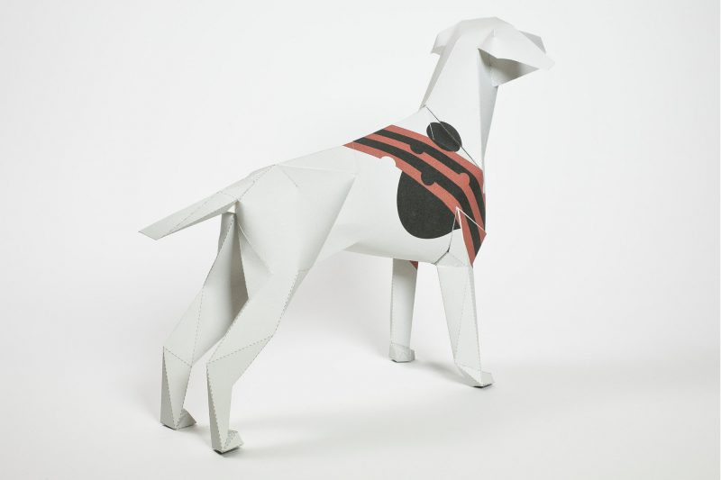 A paper dog model in 3D that has alternative red and black stripes in the middle of the dog on the torso.