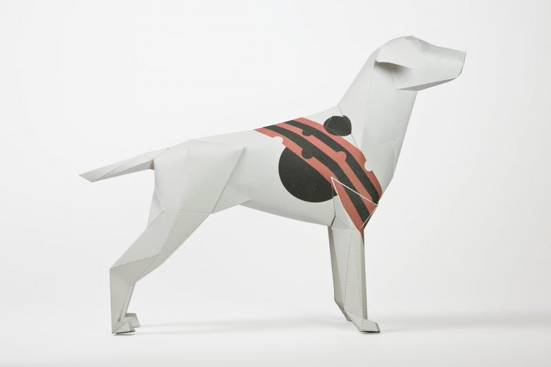 A 3D paper model of a dog which has alternating red and black stripes across its neck to its stomach.