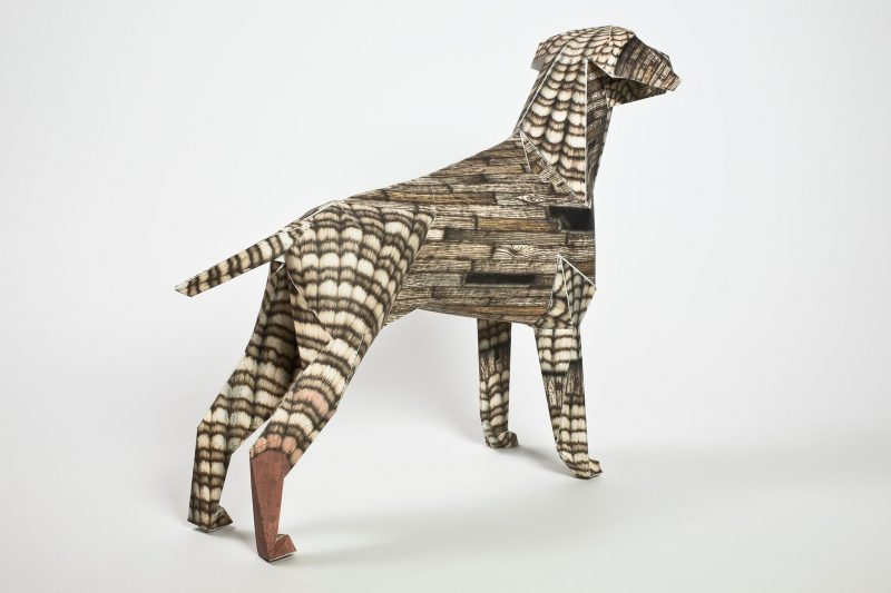 A right hand view of a paper dog 3D model with a woodgrain brown style pattern on it.