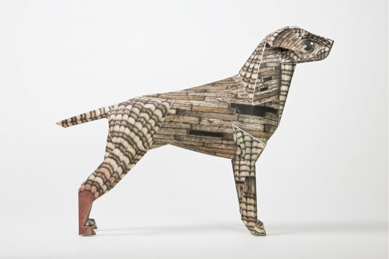 A side view of a paper dog model that is patterned in a wood grain style design,