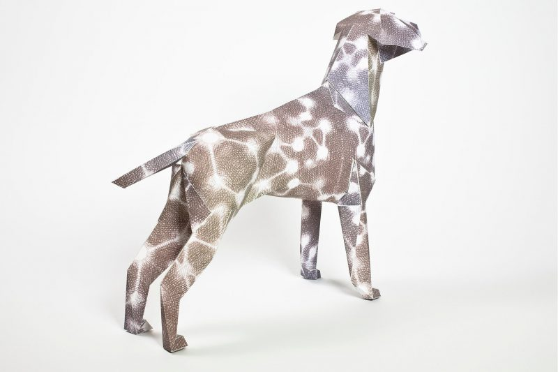 3D paper dog model with white circles and white lines that connect the circes. It also has a brownish background.