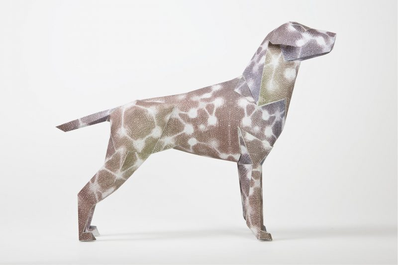 A dog made from a 3D paper model which has a brownish colour on it with white circles that are connected by white lines.