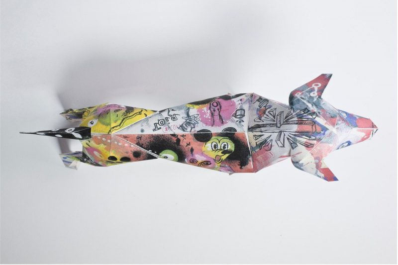 Over head view of a 3D paper dog model. The design on the paper model is a graffiti style spray