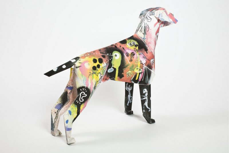 Paper dog model with a graffiti style design on it. The dog is looking away from the camera toward the right hand side.