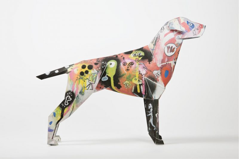 Side view of a 3D paper dog model that is covered in a graffiti design spray