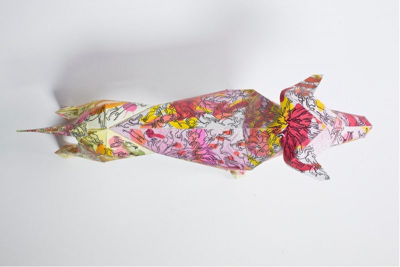 A over head view of a 3d paper model of a dog. It has a pattern all over it with the colours yellows, oranges, reds and pi
