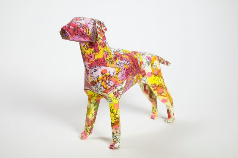 A 3D paper model of a dog as part of a art exhibition from design studio Lazerian. The design on the coat is a mixture of pinks, yellows, oranges and reds