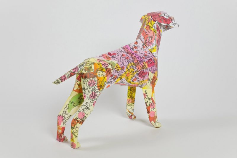 A paper dog 3D model with a pattern on its coat that consists of reds, yellows, oranges and pinks
