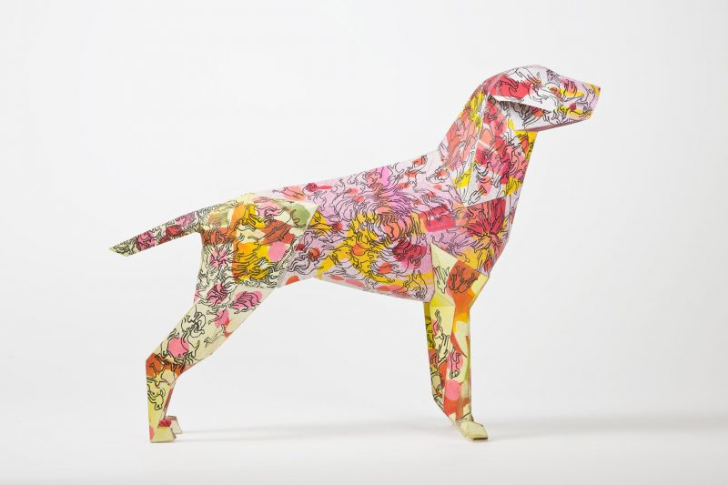 A side view of a 3D paper dog model. The coat is covered in the colours- red, yellow, pink and orange.