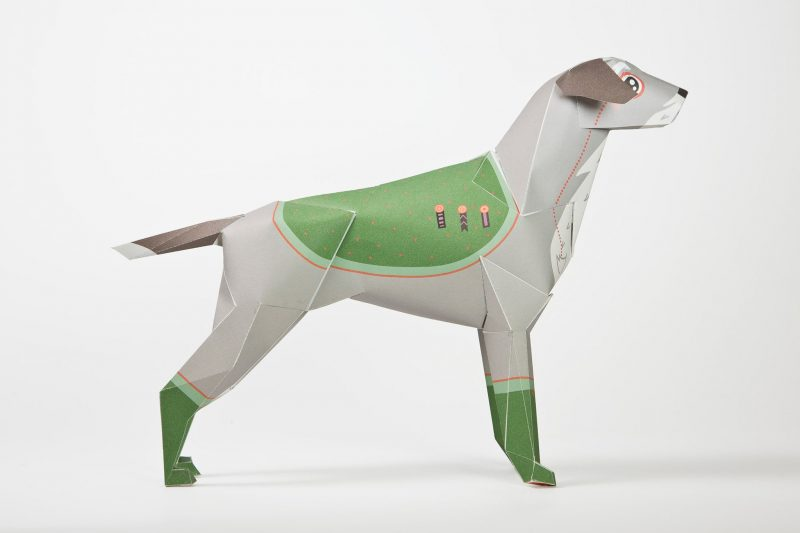 Side view of a 3D paper dog model dressed as a old style general in a army.