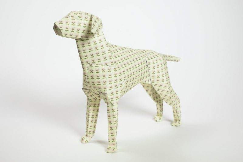 3D paper dog model with its head facing to the left hand side and stood on a angle. It has a lot of small tulip style khaki green flowers all over it.