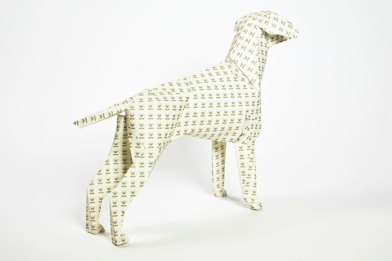 A 3D paper dog sculpture facing away from the camera to the right hand side. It has lots of miniature tulip flowers that are khaki green all over its body, legs and head.