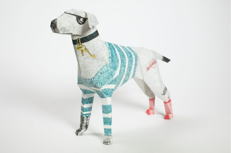 Left hand view of a paper dog model showing the dog with a eye patch and a collar with keys dangling. It also has blue lines drawn across its body