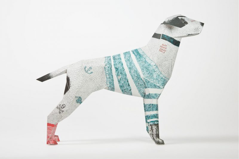 A side view of a paper dog model with the head facing to the right hand side of the screen. The dog has a design drawn over it that consists of 4 light blue stripes across its body and 'socks on its feet. The back feet are red and the front feet are dark grey. The dog has a collar drawn on its neck.