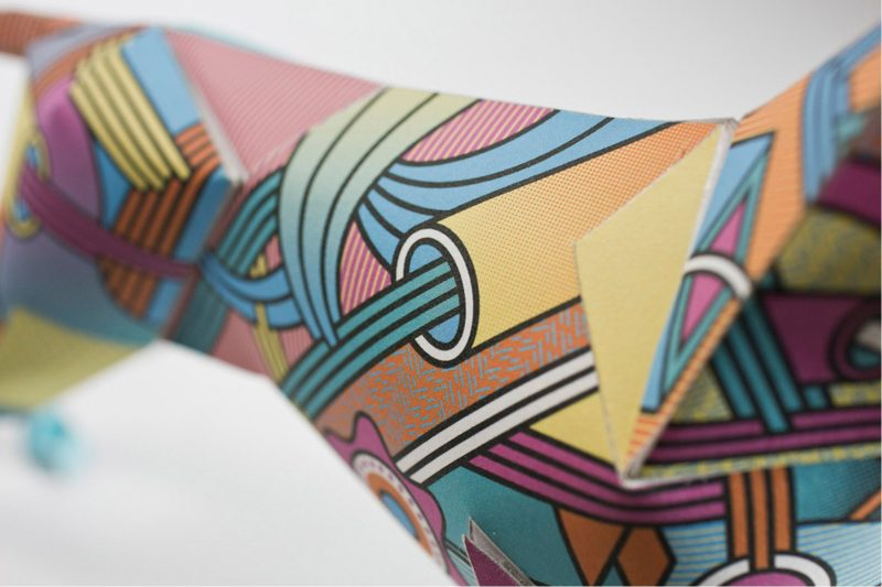 Close up of paper dog model. Showing pattern of coloured lines (blues, oranges, yellows)
