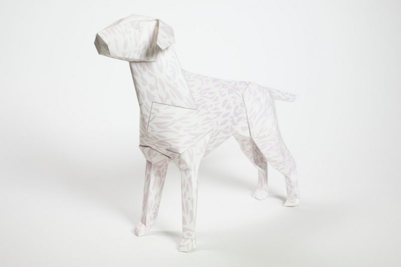 Left habd view of a aper dog sculpture. Pattern on its coat is a very light leopard print.