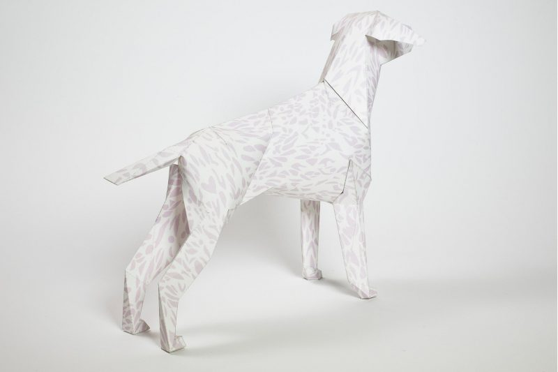 A dog model made from paper with a faint leopard print pattern on its body