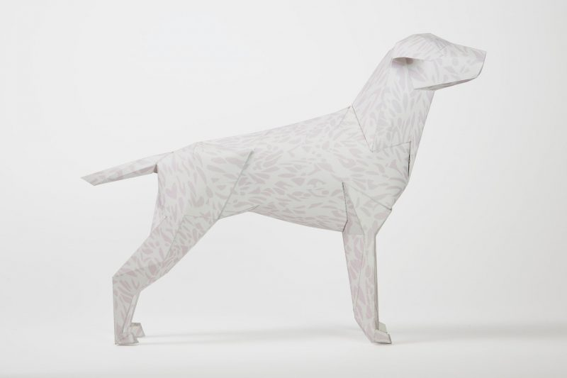 A paper dog model with a ligh and very faint leopard print on its coat.