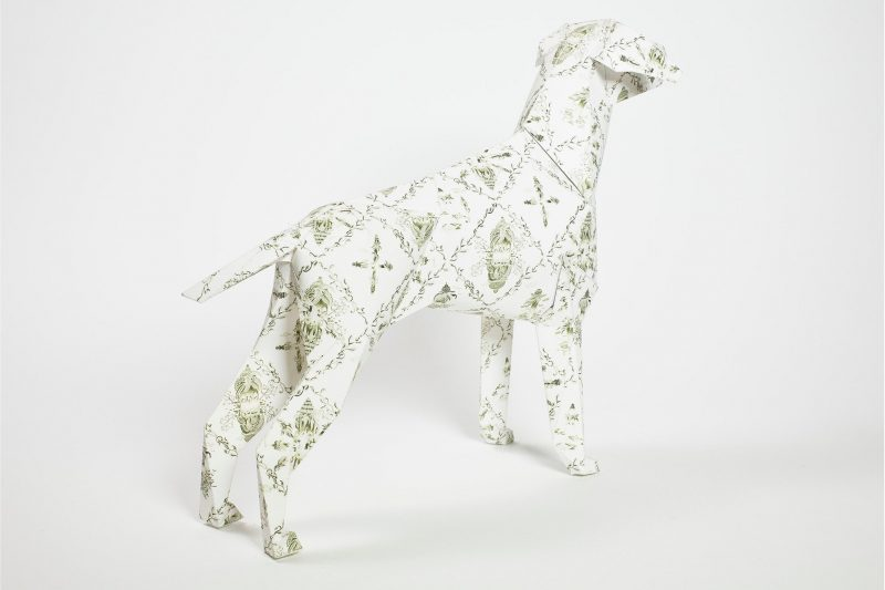 Paper dog model facing towards the back left of the photo. The pattern on the dog is slight with crosses and light in colour
